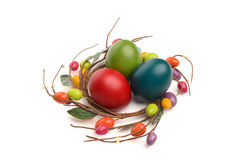 Colorful hand dyed easter eggs with circle easter egg nest decoration around them. Royalty Free Stock Images