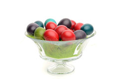 Colorful hand dyed easter eggs in a glass bowl decorated with grass. Stock Photo