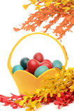 Colorful hand dyed easter eggs in a yellow basket, decorations with spring flowers Stock Images