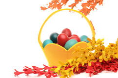 Colorful hand dyed easter eggs in a yellow basket, decorations with spring flowers Royalty Free Stock Image