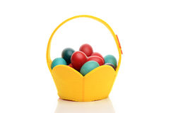 Colorful hand dyed easter eggs in a yellow basket. Stock Photos