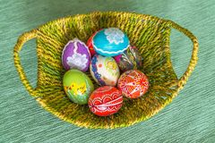 Colorful hand painted easter eggs in basket. Top view Royalty Free Stock Images