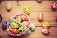 Colorful hand painted Easter eggs in basket and on wood. Handmade vintage decoration Stock Photos
