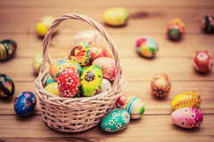 Colorful hand painted Easter eggs in basket and on wood. Handmade vintage decoration Stock Photo