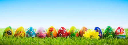 Colorful hand painted Easter eggs on grass. Banner, panoramic Stock Images