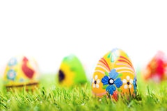 Colorful hand painted Easter eggs in grass. Spring theme, white copy-space. Traditional decoration, unique handmade design Stock Photos