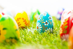 Colorful hand painted Easter eggs in grass. Spring theme, white copy-space. Traditional decoration, unique handmade design Royalty Free Stock Images