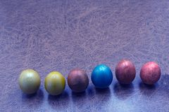 Colorful hand painted easter eggs in a row on old shabby wood for a background . stock photo