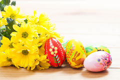 Colorful hand painted Easter eggs and spring flowers on wood Royalty Free Stock Photography