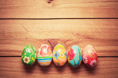 Colorful hand painted Easter eggs on wood. Unique handmade, vintage design. royalty free stock images
