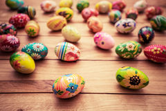 Colorful hand painted Easter eggs on wood. Unique handmade, vintage design. royalty free stock image