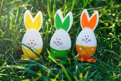Colorful hand painted eggs lie in spring green grass under the sunlight. Egg hunt decor. Festive spring background. royalty free stock image