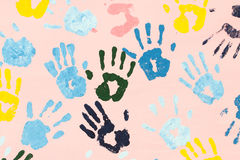 Colorful hand prints on pink wall. For background , cover , card , etc stock photography