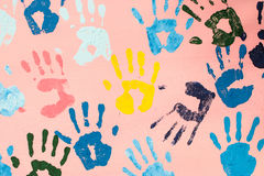 Colorful hand prints on pink wall. For background , cover , card , etc stock photos