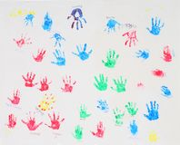Colorful hand prints on white. Colorful children's hand prints stamped on white cloth with names stock photos