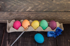 Colorful handmade easter egg with painting brush on wooden table Stock Photo