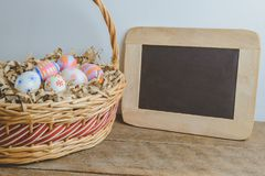 Colorful handmade easter eggs on Straw paper in basket and chalk. Board wooden table background Stock Photos