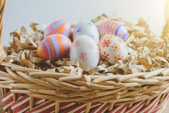 Colorful handmade easter eggs on Straw paper in basket. Wooden table background Royalty Free Stock Images