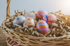 Colorful handmade easter eggs on Straw paper in basket. Wooden table background Royalty Free Stock Photo