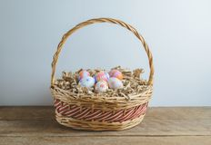 Colorful handmade easter eggs on Straw paper in basket. Wooden table background Royalty Free Stock Image