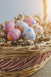Colorful handmade easter eggs on Straw paper in basket. Wooden table background Stock Photography