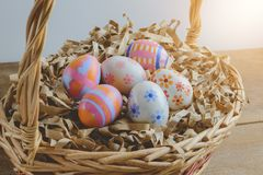 Colorful handmade easter eggs on Straw paper in basket. Wooden table background Stock Photos