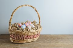 Colorful handmade easter eggs on Straw paper in basket. Wooden table background Stock Image