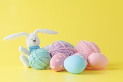 Colorful handmade easter eggs with wool clew and toy rabbit Stock Photos