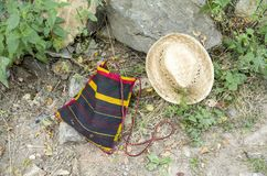 Colorful handmade wool weaving bag and straw hat on ground, Bulgaria. Colorful handmade wool weaving bag and straw hat on the ground, Bulgaria royalty free stock image
