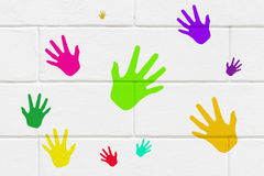 Colorful handprints on wall. Conceptual image of playing, ethnicity and teambuilding royalty free stock image
