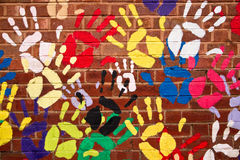 Colorful hands on a brickwall Stock Image