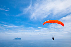 Colorful hang glider in sky. Colorful hang glider in sunny sky Stock Photo