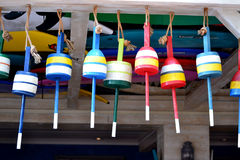 Colorful Hanging Buoys. Buoys hanging from the ceiling of a porch among surfboards Stock Images