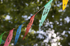 Colorful hanging decorations. Colorful overhead decorations hanging from a line between trees stock image