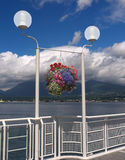 Colorful hanging flower basket. Against a dramatic sky and sea scape, Canada Place Vancouver Canada Royalty Free Stock Image