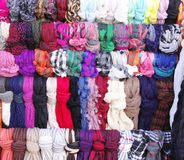 Colorful hanging scarves in shop Stock Images