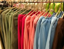 Colorful hanging woman linen pants on rack. Colorful hanging woman linen  pants on rack in shopping store Stock Image