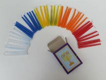 Colorful Hannukah candles creating the shape of a rainbow with a sign of a lamp on the open candle box stock image