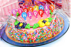 Colorful Happy Birthday Cake. Beautiful and colorful Happy Birthday Cake surrounded with gifts and festively decorated stock photography