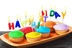 Colorful happy birthday cupcakes with candles Stock Photos
