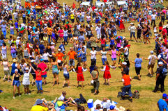 Colorful happy dancing people amusement. Vibrant picture of ubiquitous merriment of thousands of people  dancing cheerfully at Rozhen Folklore Festival on Stock Photo