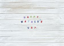 Colorful Happy mathers day sign. On white wooden boards background royalty free stock photo