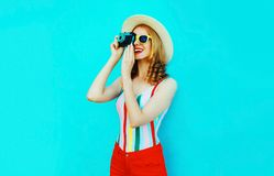 Colorful happy smiling young woman holding retro camera in summer straw hat having fun on blue wall stock photography