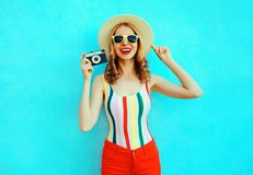 Colorful happy smiling young woman holding retro camera in summer straw hat having fun on blue wall stock photos