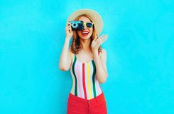 Colorful happy smiling young woman holding retro camera in summer straw hat having fun on blue wal royalty free stock image