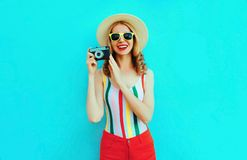 Colorful happy smiling young woman holding retro camera in summer straw hat having fun on blue wall royalty free stock photos