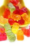 Colorful haribo bear candies pouring out of yellow bowl Royalty Free Stock Image