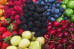 Colorful harvest of summer berries and fruits. Top view and soft focus. Assorted fresh bright and juicy berries - blueberries, strawberries, raspberries Stock Image