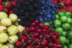 Colorful harvest of summer berries and fruits. Top view and soft focus. Assorted fresh bright and juicy berries - blueberries, strawberries, raspberries Stock Photos