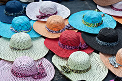 Colorful Hats. Brightly colored wide brimmed ladies straw sun hats for sale at the beachfront Stock Photos